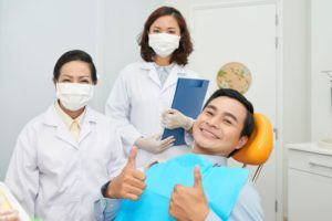 smiling-patient-and-doctors-in-dental-office-932G46R